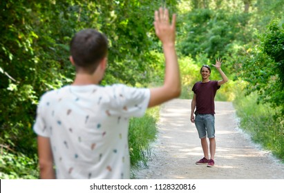Two friends waving to each other in nature