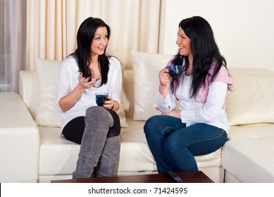 Two friends women sitting on couch   holding cups of coffee and having conversation in a living room