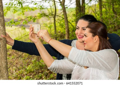 Two friends women taking selfie with smartmobile in forest in sunny day