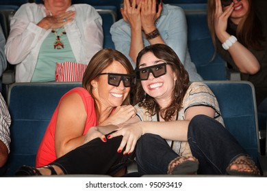 Two frightened women with 3D glasses get close together