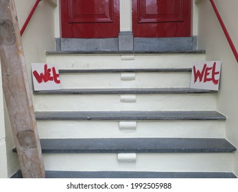 two front doors and railings been painted red, with warning 'wet'