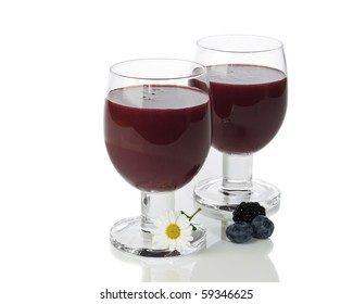 Two fruit smoothies on white background with flower and blueberries