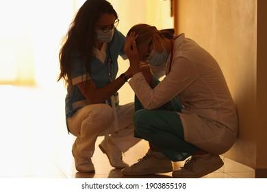 Zwei frustrierte Ärzte in medizinischen Schutzmasken sitzen im Krankenhauskorridor. Unregelmäßige Arbeitszeiten für Beschäftigte des Gesundheitswesens nach dem Konzept der Koronavirus-Pandemie