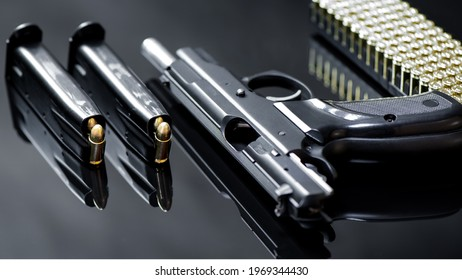 Two full loaded magazine with 9 mm pistol and luger ammunitions on a black mirror base.