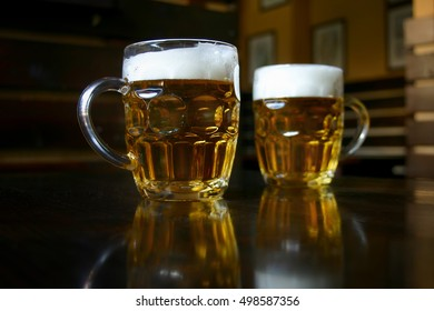 Two full mugs of beer atop a wooden table