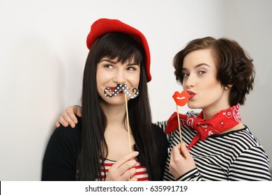 Two fun attractive elegant young ladies with party accessories holding a polka dot mustache and luscious red lips respectively as they stand arm in arm