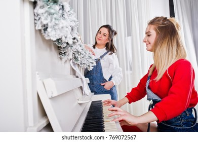 Two fun beautiful girls friends wear in overalls jeans shorts and gaiters against piano with new year decoration.