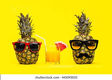 Two Fun Fashion pineapples with sunglasses and mustache with fresh tropical cocktail with fruit over yellow background. Husband and wife. Boy and girl. Vacation and travel trip concept.