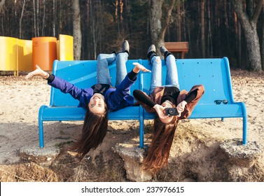 Two funky friends having fun and taking photos lying upside down on a bench on the beach. Outdoor lifestyle portrait