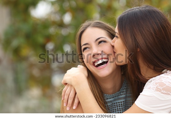Two funny affectionate women friends laughing and kissing outdoors