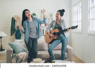 two funny asian girls dancing singing and playing acoustic guitar in living room. happy Sisters having fun leisure with music at home. beautiful ladies relax enjoy together with popcorn and beers