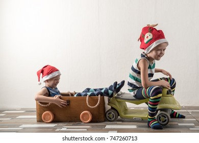 Two funny boys in a Santa Claus hat are playing in a plywood box. Guys have fun at home. Christmas holiday concept. Copy space.