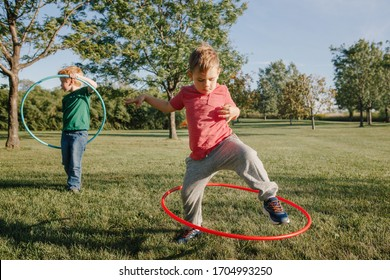 Two funny Caucasian preschool boys playing with hoola hoop in park outside. Kids sport activity. Lifestyle happy childhood. Summer seasonal outdoor game fun for kids children.