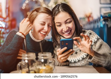 Two funny female friends look at new memes on social networks and laugh out loud in cafe. Smartphone with online Internet access - a new type of leisure for group of friends