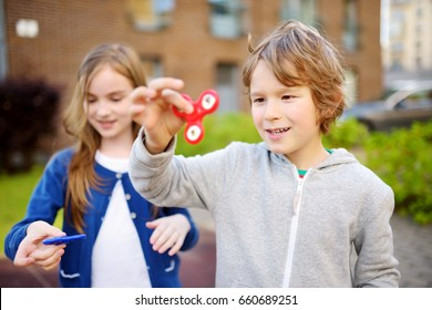 Two funny friends playing with colorful fidget spinners on the playground. Popular stress-relieving toy for school kids and adults.