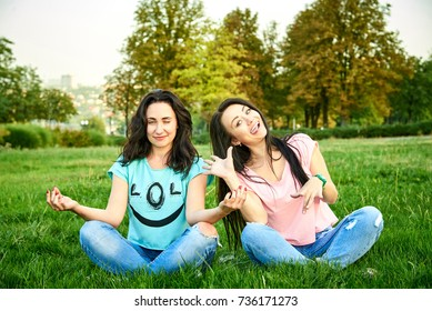 Two funny girlfriends girls sit on the grass in a lotus pose and show grimaces