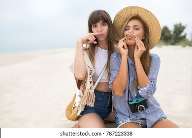 Two funny girl,playful mood,attractive girls, cheerful best friends enjoy time, having fun,make pictures,Wearing shiny dresses with paillettes, fashionable looking,make mustache,straw hat,boho style