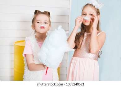 Two funny girls with cotton candy posing on a children's holiday