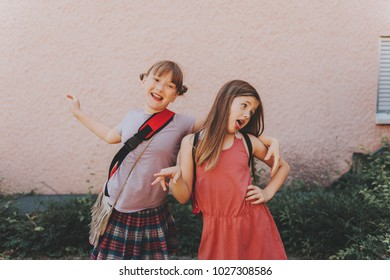Two funny girls making grimace, silly schoolgirls playing together after school