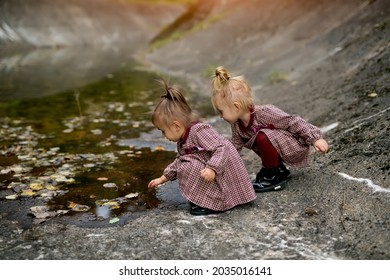 Two funny girls on a rocky shore are picking at autumn puddles with a stick. The leaves fall directly into the water. It's fun to play on the rocks together in identical dresses.
