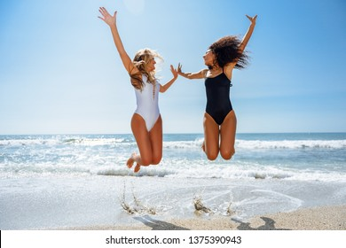 Two funny girls in swimsuit jumping on a tropical beach in summer.