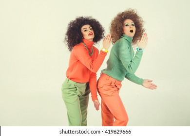 Two funny girls wearing retro clothes in studio. Disco diva over white background