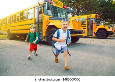 Two funny happy Caucasian boys students kids running near yellow bus on 1 September day. Education and back to school concept. Children friends pupils ready to learn and study.
