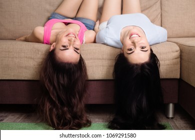 Two funny and happy girl friends or sisters are lying on the couch upside down and having fun