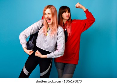 Two funny hipster young woman showing biceps, studio blue background, sportive fitness clothes, exited emotions, couple going crazy together.