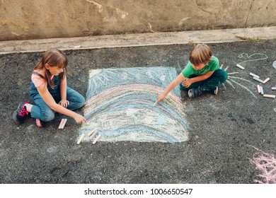 Two funny kids drawing with chalk, children playing together, top view
