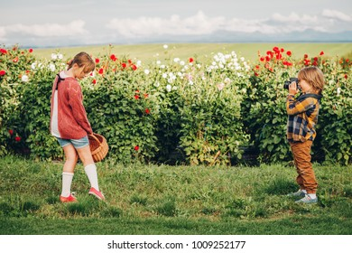 Two funny kids playing together in beautiful chrysanthemum garden. Little handsome boy with camera taking pictures of his cute sister. Family time in countryside, hobby and leisure