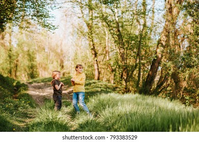 Two funny kids playing together in spring forest, little brother and sister enjoying nice walk in woods