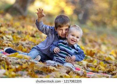 Two funny kids posing outdoors. Early autumn.
