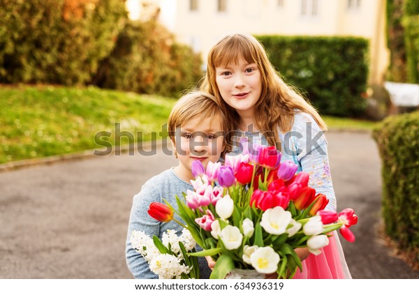 Two funny kids with spring flowers. LIttle boy and his big sister holding big beautiful bouquet of colorful tulips. Mother's day concept