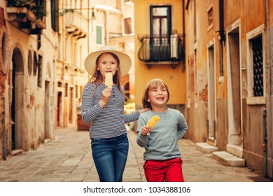Two funny kids walking through old italian streets, family tavel with children. Kids eating ice cream