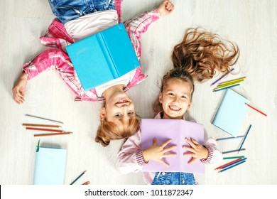 Two funny little girls with books. Flat lay. The concept of childhood, learning, friendship, family, school, lifestyle.