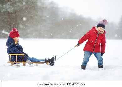 Two funny little girls having fun with a sleigh in beautiful winter park. Cute children playing in a snow. Winter activities for kids.