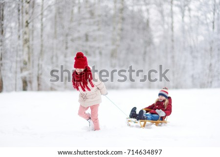 Two funny little girls having fun with a sleight in beautiful winter park. Cute children playing in a snow. Winter activities for kids.