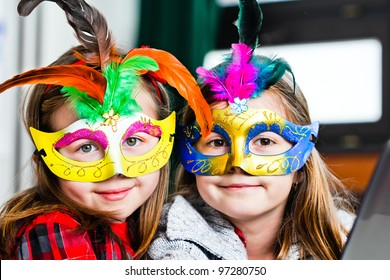 Two funny little girls with masks