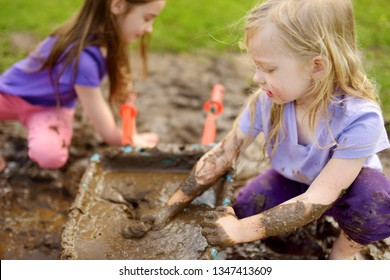 Two funny little girls playing in a large wet mud puddle on sunny summer day. Children getting dirty while digging in muddy soil. Messy games outdoors.