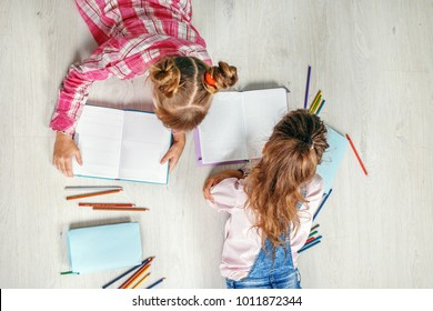 Two funny little girls read and write. Flat lay. The concept of childhood, learning, friendship, family, school, lifestyle.