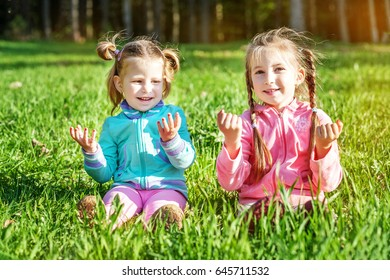 Two funny little Kids are playing on the grass. The concept of childhood and lifestyle.