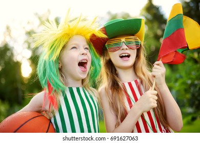 Two funny little sisters supporting and cheering their national basketball team during basketball championship. Two cute Lithuanian team fans.
