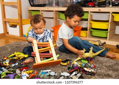 Two funny and messy baby brothers playing together in kids room