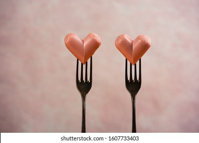 Two funny sausages forming a hearts on a forks on pink background. Wedding or St Valentines day concept. Horizontal, copy space