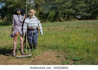 Two funny scarecrows in the field. Pair of scarecrows with hat and stick. Harvest protection and security concept. Rural landscape. Farm guard. Outdoor security dolls in meadow.