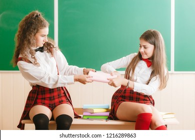 Two funny schoolgirls in school uniforms are sitting on the background of a green board on the desk with books.girls fighting for one book