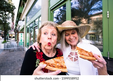 Two funny senior women eating street food pizza