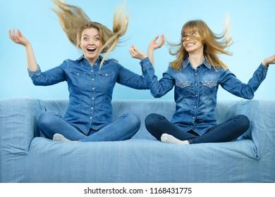 Two funny shocked women wearing jeans shirts having windblown blonde hair. Blue background.