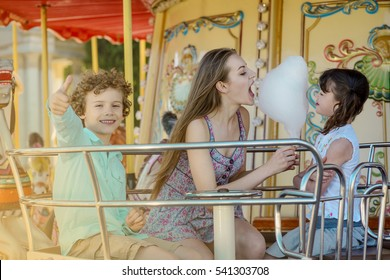 Two funny sisters eat the cotton candy together, the elder girl bites the fluffy dessert. Little boy shows OK gesture and looks in the camera with sincere smile.